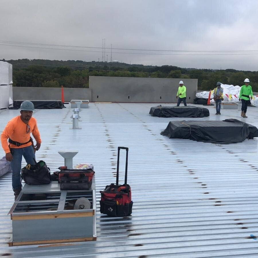 Man on commercial building roof